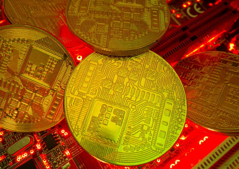 Representations of the virtual currency stand on a motherboard in this picture illustration