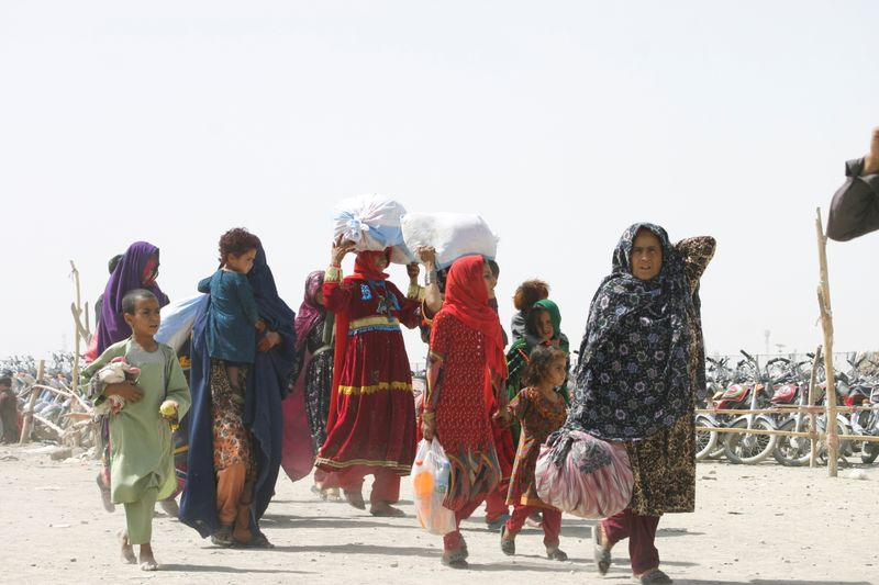 People from Afghanistan cross the 'Friendship Gate' in the Pakistan-Afghanistan border town of Chaman