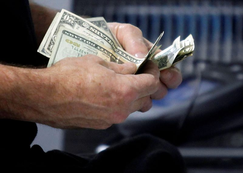 FILE PHOTO: FILE PHOTO: A customer counts his cash at the register while purchasing an item at a Best Buy store in Flushing