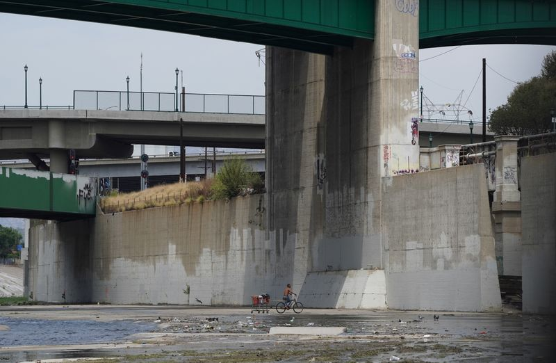 A man experiencing homelessness pulls a shopping cart on his bicycle in the Los Angeles River in Los Angeles