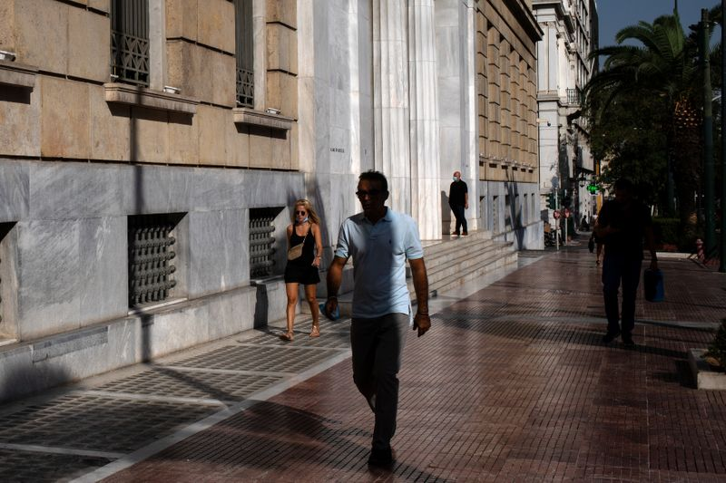 People make their way outside the headquarters of Bank of Greece in Athens