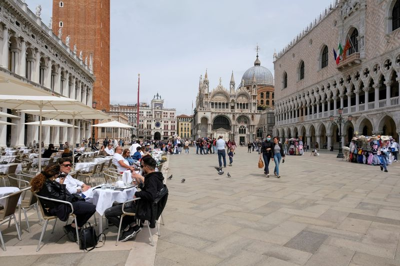 FILE PHOTO: People sit at outdoor tables in St. Mark's Square, Venice, Italy