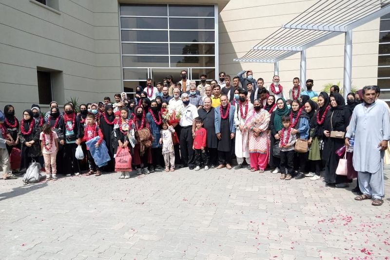 Afghan women's soccer team along with their families pose for a group photo upon their arrival in Lahore