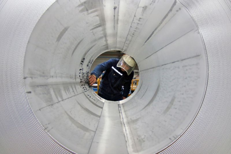 FILE PHOTO: Employee works at the production line of aluminium rolls at a factory in Zouping