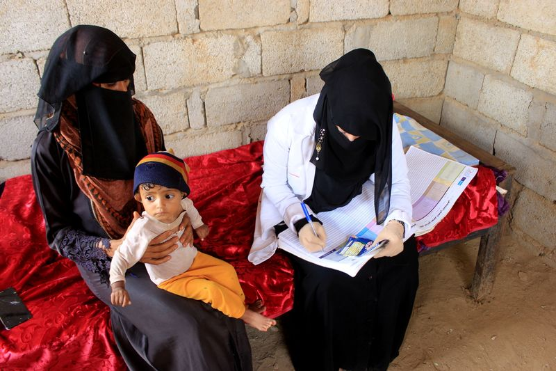 Volunteer health worker Ashwaq Muharram obtains the information about a boy as she assesses his nutritional status in Abs