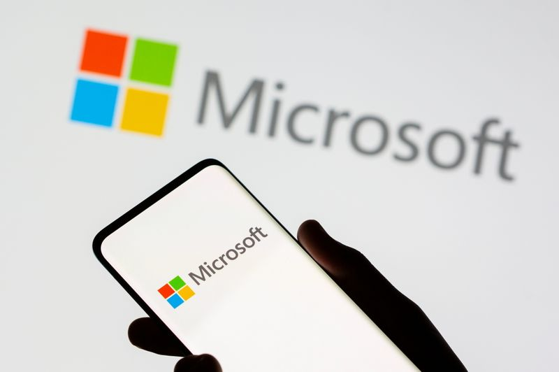FILE PHOTO: A smartphone is seen in front of a Microsoft logo displayed in this illustration