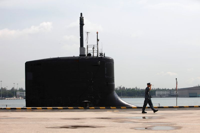 US Navy personnel pass in front of the USS North Carolina submarine docked at Changi Naval Base in Singapore