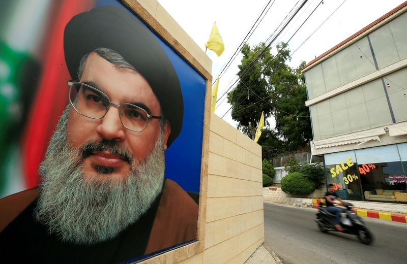 FILE PHOTO: A man rides a motorbike in front of a photo of Lebanese Hezbollah leader Sayyid Hassan Nasrallah, near Sidon