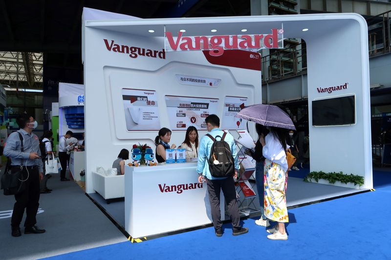 People are seen at a booth of Vanguard Group at a fair during the INCLUSION fintech conference in Shanghai