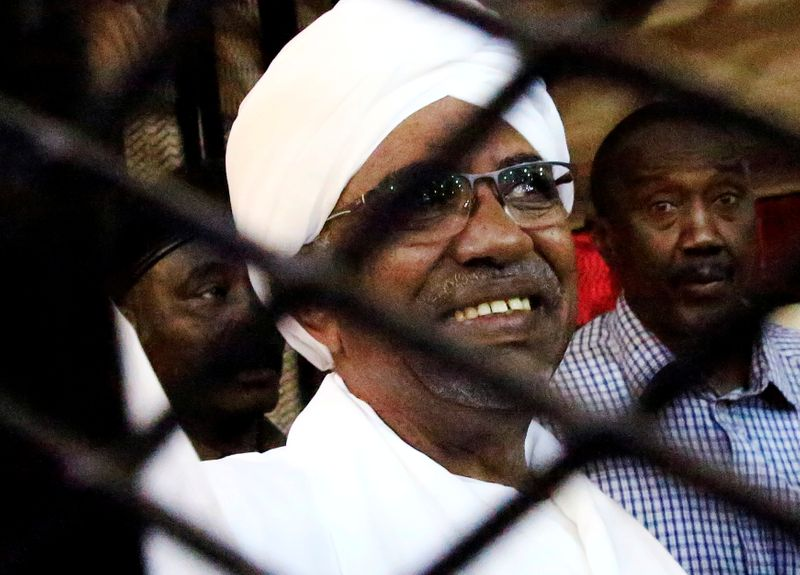 FILE PHOTO: Sudan's former president Omar Hassan al-Bashir smiles as he is seen inside a cage at the courthouse where he is facing corruption charges, in Khartoum