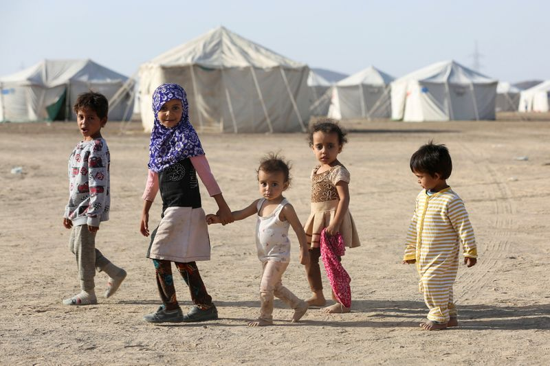 Children walk at a camp for people recently displaced by fighting in Yemen's northern province of al-Jawf between government forces and Houthis, in Marib