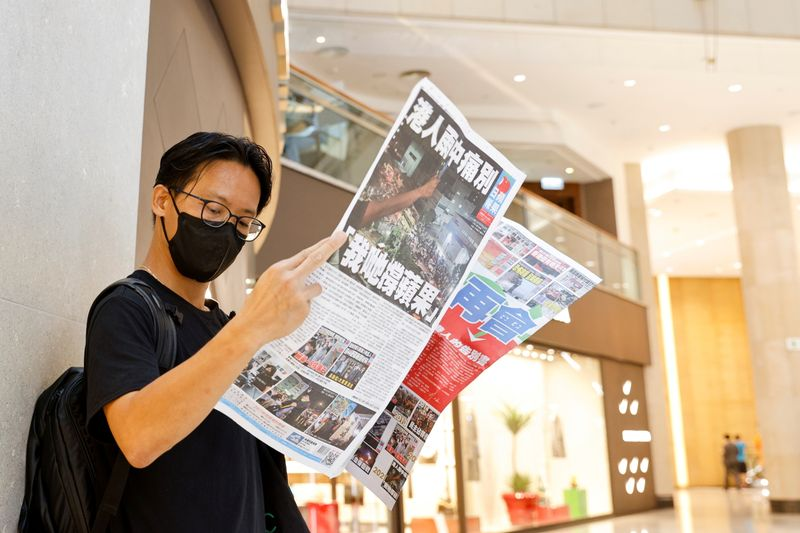 FILE PHOTO: An Apple Daily supporter reads the final edition of the newspaper at a shopping mall in Hong Kong
