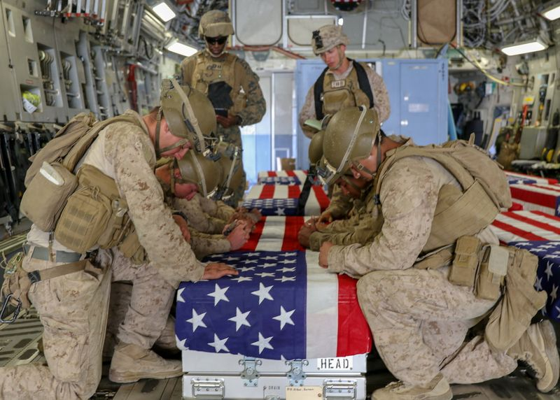 U.S. Marines honor their fallen service members killed in action during a ramp ceremony in Kabul
