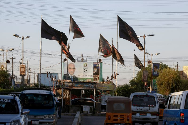 Religious flags are pictured near an election campaign poster ahead of the parliamentary election, in Baghdad