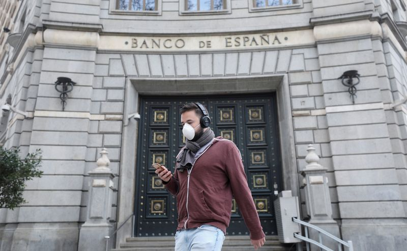A man wears a protective face mask as he walks past Banco de Espana (Bank of Spain), amidst concerns over coronavirus outbreak, in Barcelona