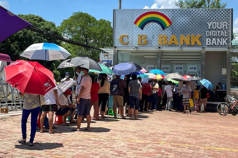 FILE PHOTO: People line up outside a bank to withdraw cash, in Yangon