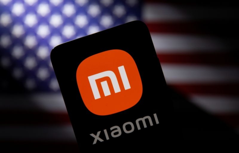 FILE PHOTO: Smartphone with a Xiaomi logo is seen in front of U.S. flag in this illustration