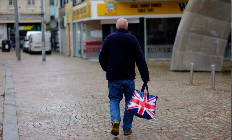 A man carries a Union Jack themed shopping bag as he walks along an empty shopping street in Blackpool