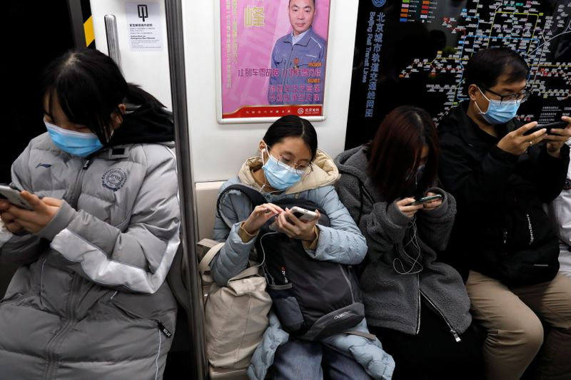 FILE PHOTO: People wearing protective face masks look at their mobile phones on a subway train, following the new cases of the coronavirus disease (COVID-19) in Beijing