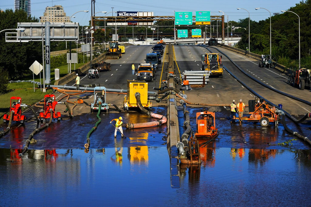Workers pump water from a flooded section of Interstate 676 in Philadelphia Friday, Sept. 3, 2021 in the aftermath of downpours and high winds from the remnants of Hurricane Ida that hit the area. The cleanup and mourning has continued as the Northeast U.S. recovers from record-breaking rainfall from the remnants of Hurricane Ida. (AP Photo/Matt Rourke)
