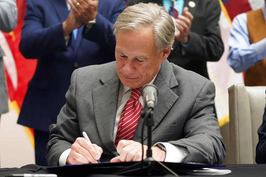 Texas Gov Greg Abbott signs Senate Bill 1, also known as the election integrity bill, into law in Tyler, Texas, Tuesday, Sept. 7, 2021. The sweeping bill signed Tuesday by the two-term Republican governor further tightens Texas' strict voting laws. (AP Photo/LM Otero)