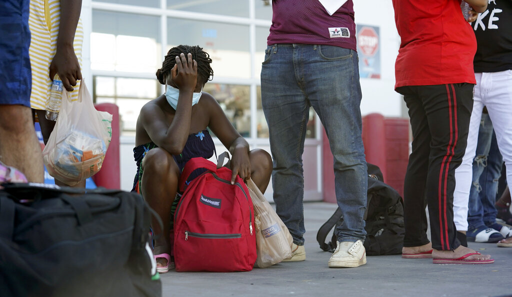 Migrants, mostly from Haiti, wait for a bus after they were processed and released after spending time at a makeshift camp near the International Bridge, Sunday, Sept. 19, 2021, in Del Rio, Texas. The U.S. flew Haitians camped in the Texas border town back to their homeland Sunday and tried blocking others from crossing the border from Mexico in a massive show of force that signaled the beginning of what could be one of America's swiftest, large-scale expulsions of migrants or refugees in decades. (AP Photo/Eric Gay)