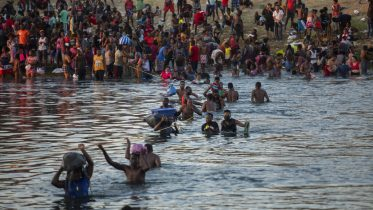 Migrants, many from Haiti, wade across the Rio Grande from Del Rio, Texas, to return to Ciudad Acuña, Mexico, Sunday, Sept. 19, 2021, to avoid deportation to Haiti from the U.S. The U.S. is flying Haitians camped in a Texas border town back to their homeland and blocking others from crossing the border from Mexico in a massive show of force that signals the beginning of what could be one of America's swiftest, large-scale expulsions of migrants or refugees in decades. (AP Photo/Felix Marquez)