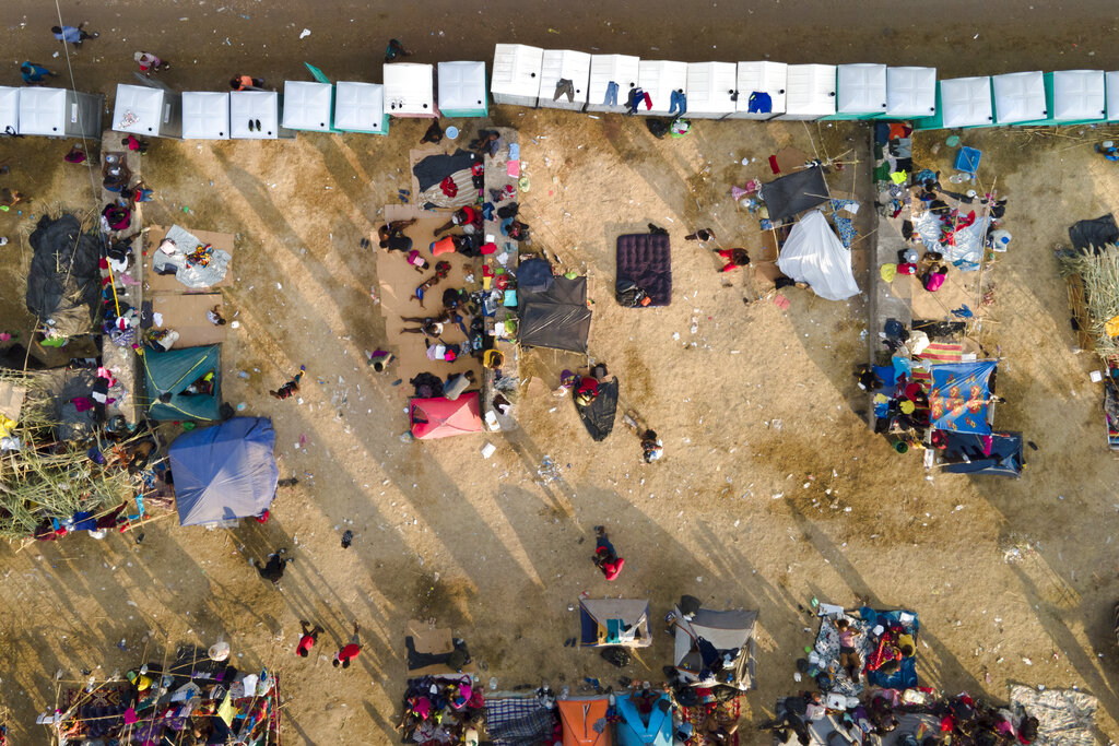 Migrants, many from Haiti, are seen at an encampment along the Del Rio International Bridge near the Rio Grande, Tuesday, Sept. 21, 2021, in Del Rio, Texas. The U.S. is flying Haitians camped in a Texas border town back to their homeland and blocking others from crossing the border from Mexico. (AP Photo/Julio Cortez)