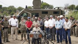 Texas Gov. Greg Abbott, center, speaks during a news conference along the Rio Grande, Tuesday, Sept. 21, 2021, in Del Rio, Texas. The U.S. is flying Haitians camped in a Texas border town back to their homeland and blocking others from crossing the border from Mexico. (AP Photo/Julio Cortez)