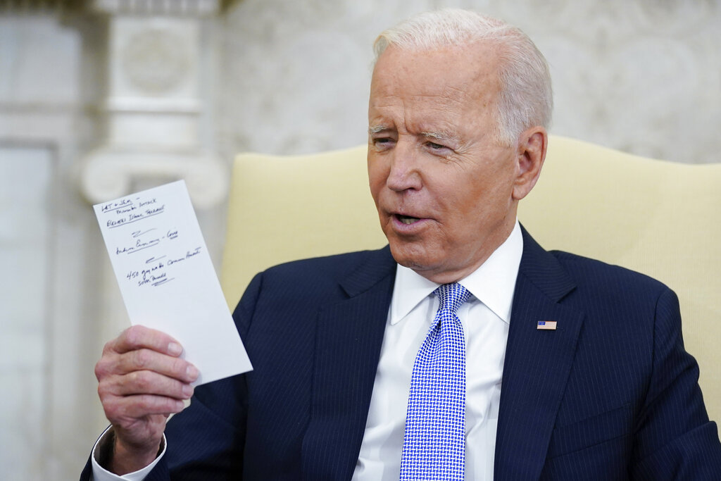 President Joe Biden holds notes as he meets with Indian Prime Minister Narendra Modi in the Oval Office of the White House, Friday, Sept. 24, 2021, in Washington. (AP Photo/Evan Vucci)