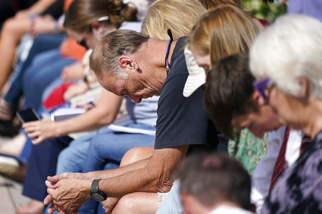 People pray during a vigil at the Collierville Town Hall Friday, Sept. 24, 2021, in Collierville, Tenn. The vigil is for the person killed and those injured when a gunman attacked people in a Kroger grocery store Thursday before he was found dead of an apparent self-inflicted gunshot wound. (AP Photo/Mark Humphrey)