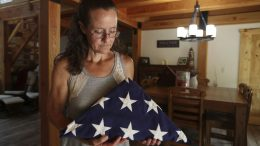 Gretchen Catherwood holds the flag that draped the casket of her son, Marine Lance Cpl. Alec Catherwood, in Springville, Tenn., on Wednesday, Aug. 18, 2021. In 2010, Alec, 19, was killed in Afghanistan fighting the Taliban. When he was alive, she loved to touch his face. He had baby soft skin and when she put her hands on his cheeks, this big tough Marine felt like her little boy. (AP Photo/Karen Pulfer Focht)