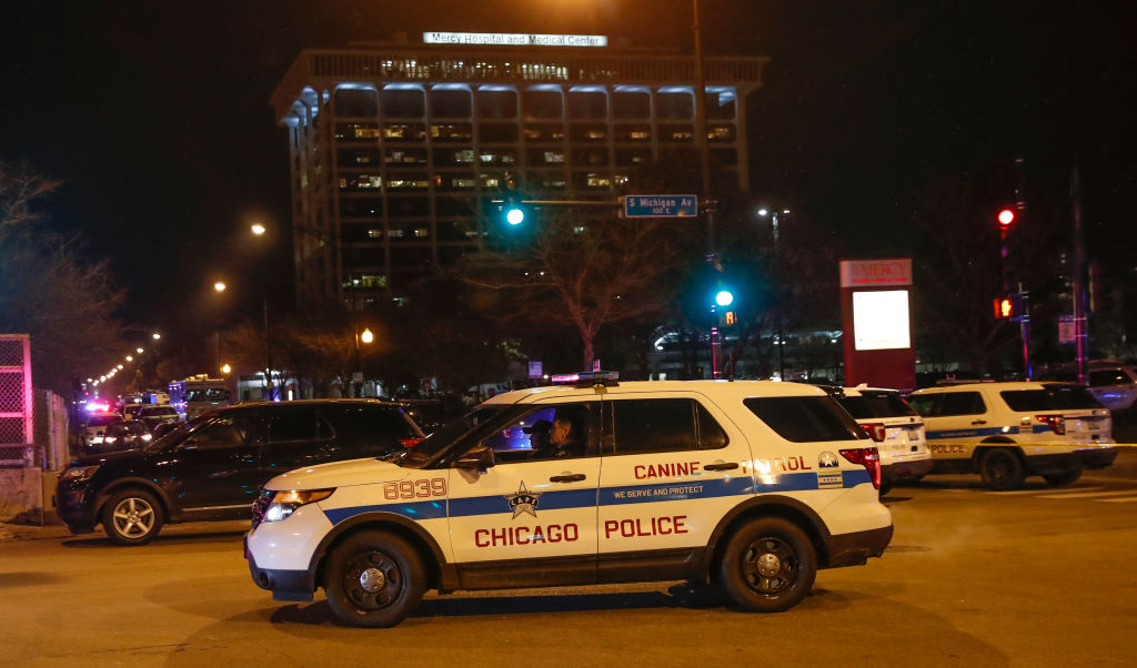 """Chicago Police officers monitor the area outside of the Chicago Mercy Hospital where a gunman opened fire in Chicago on November 19, 2018. - An argument in a hospital parking lot escalated into a shooting that killed three people, including a police officer, in the US city of Chicago on November 19, 2018. The violence only ended when police engaged in shootout with the gunman inside Mercy Hospital. """"We have four deceased individuals: police officer, two female staff employees at the hospital, and the offender,"""" police Superintendent Eddie Johnson told journalists. (Photo by KAMIL KRZACZYNSKI / AFP) (Photo credit should read KAMIL KRZACZYNSKI/AFP via Getty Images)"""