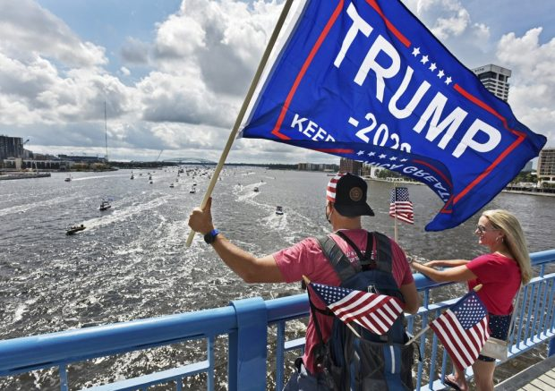 Brian Masotti, left, and Tracey Warren wave flags at the hundreds of boats idling on the St. Johns River during a rally Sunday, June 14, 2020, in Jacksonville, Fla., celebrating President Donald Trump's birthday. (Will Dickey/The Florida Times-Union via AP)