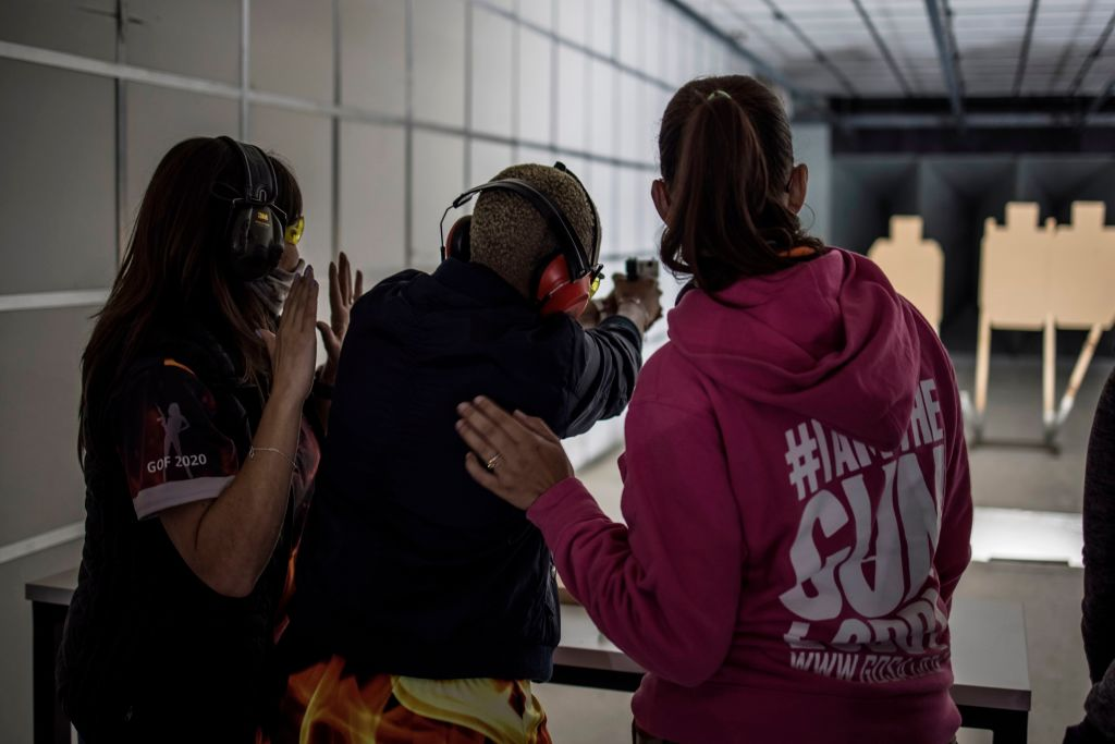 Two instructors prepare to contrast the recoil from a loaded pistol fired by a South African woman as she takes part in a training organised by the women empowerment group Girls on Fire, in Midrand, on February 07, 2021. - Gun Owners of South Africa's (GOSA) Girls on Fire campaign was created in 2015 to coincide with the 16 days of Activism from the United Nations. For the dozens of women part of this campaign learning how to master a firearm is a way of protecting themselves in a country where a woman is murdered every three hours. (Photo by MARCO LONGARI / AFP) (Photo by MARCO LONGARI/AFP via Getty Images)