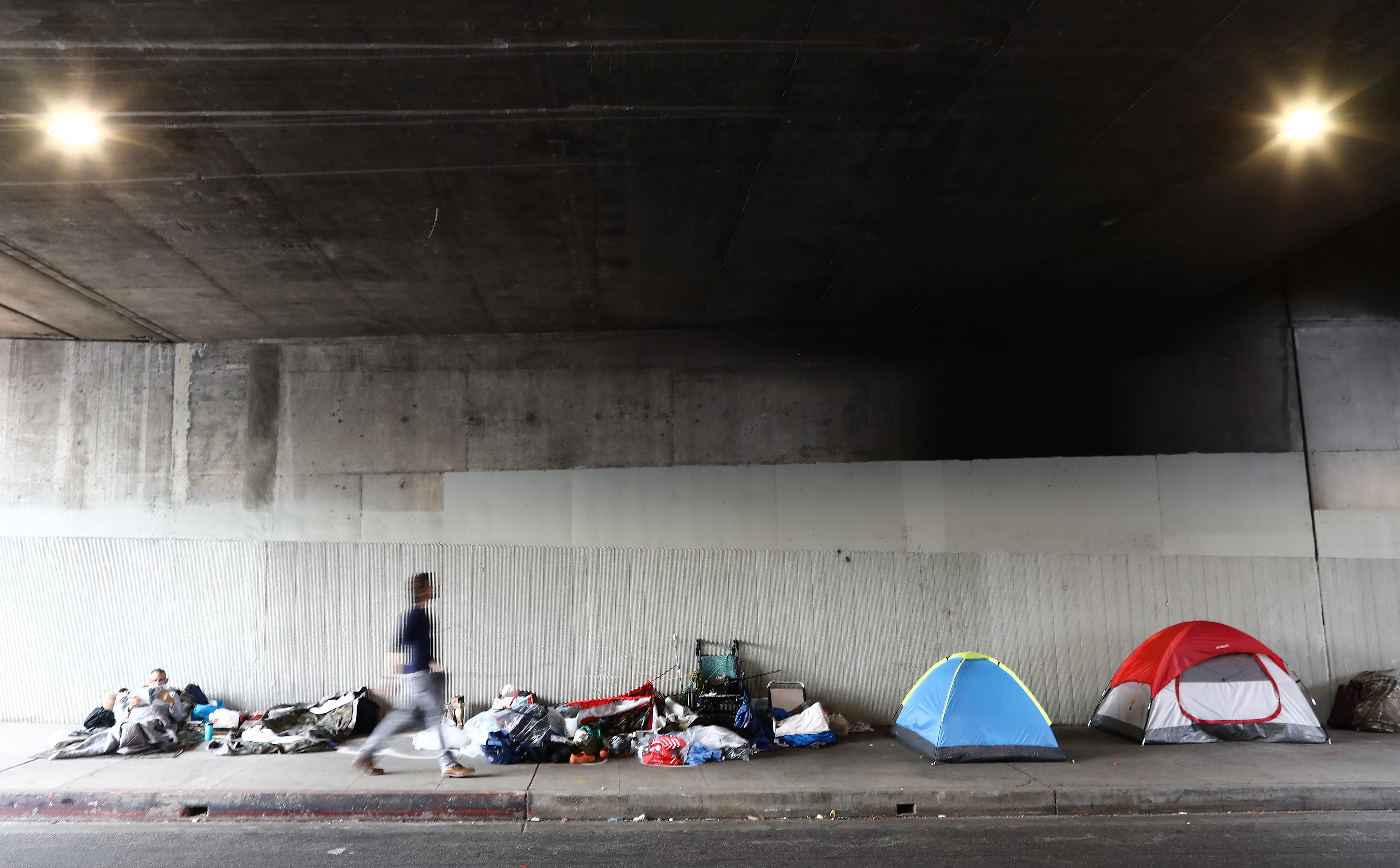 A man walks past a homeless encampment beneath an overpass in Los Angeles, California. (Photo by Mario Tama/Getty Images)