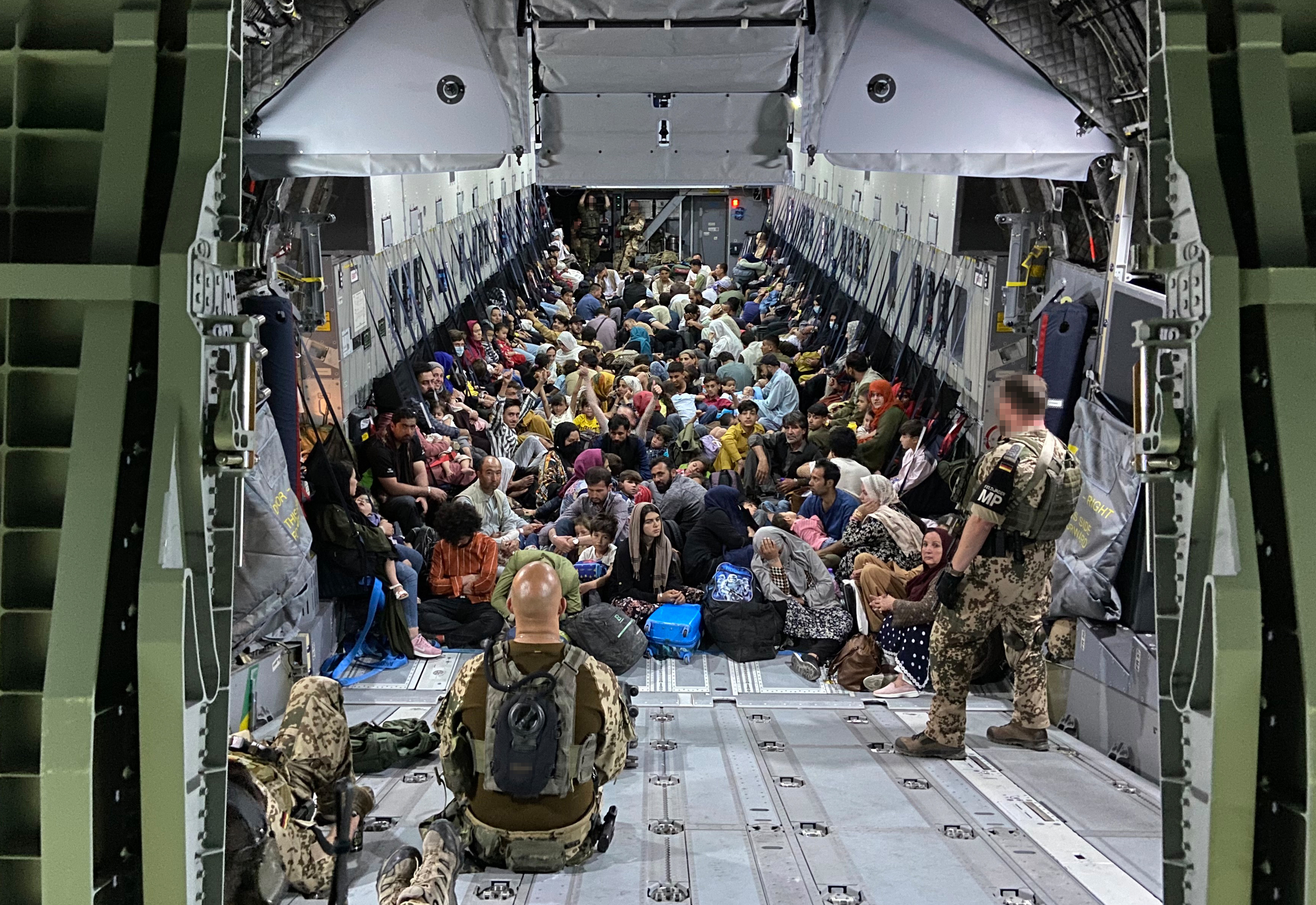In this handout image provided by the Bundeswehr, evacuees from Kabul sit inside a military aircraft as they arrive at Tashkent Airport in Tashkent, Uzbekistan. (Photo by Handout/Bundeswehr via Getty Images)
