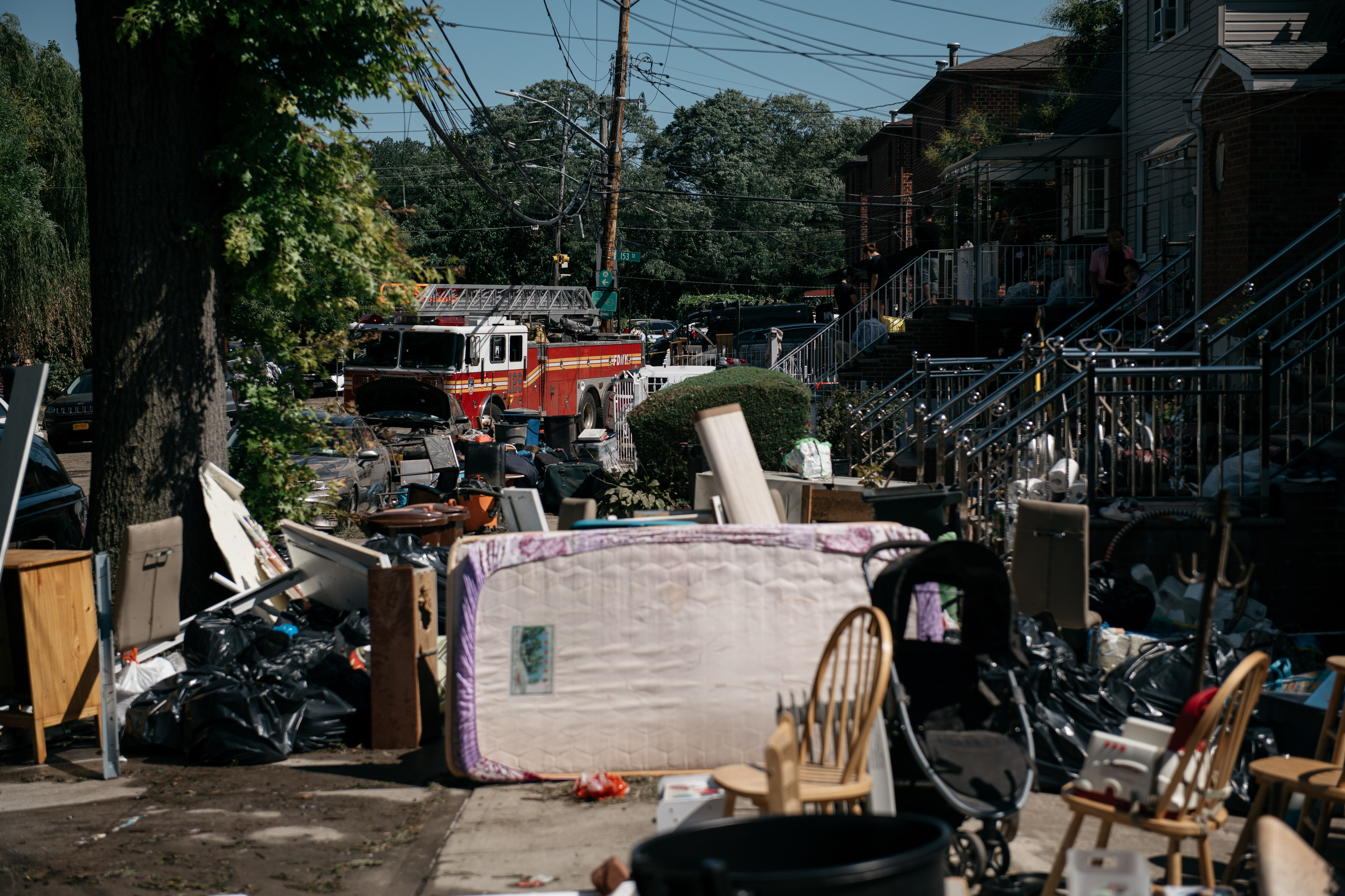 Residents sort through damaged and destroyed items after a night of heavy rain and wind caused many homes to flood in the Flushing neighborhood of the Queens borough of New York City. (Photo by Scott Heins/Getty Images)