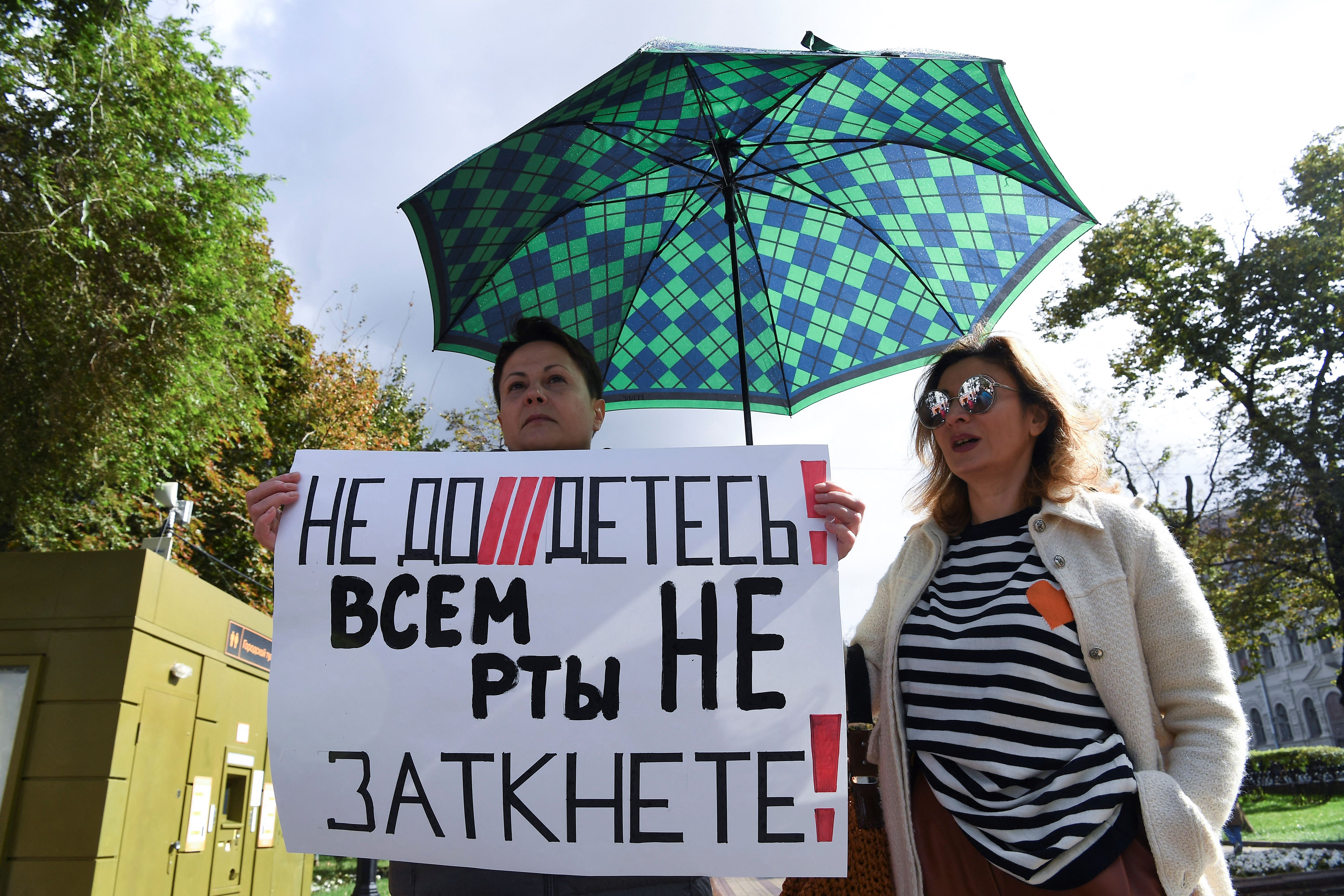 """A woman holds a placard reading """"You can't shut up everyone!"""" as journalists and supporters take part in a protest against the list of """"foreign agent"""" media in central Moscow. (Photo by NATALIA KOLESNIKOVA/AFP via Getty Images)"""