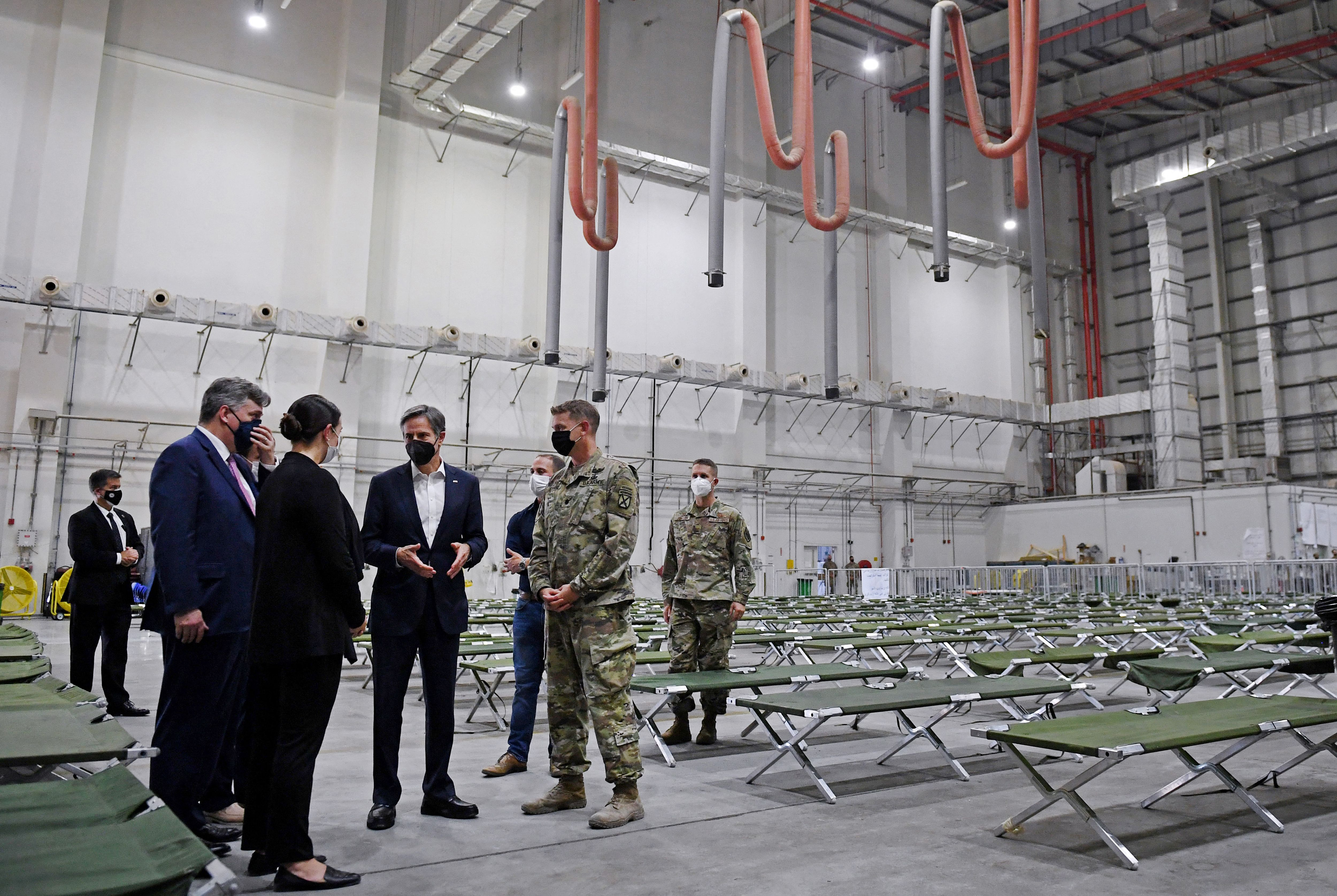 Secretary of State Antony Blinken (left) tours a processing centre for Afghan refugees at al-Udeid Air Base in the Qatari capital Doha. (Photo by OLIVIER DOULIERY/POOL/AFP via Getty Images)