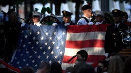 New York police and firefighters hold a US flag as a band plays the US National Anthem at the National 9/11 Memorial during a ceremony commemorating the 20th anniversary of the 9/11 attacks on the World Trade Center, in New York, on September 11, 2021. (Photo by ED JONES/POOL/AFP via Getty Images)