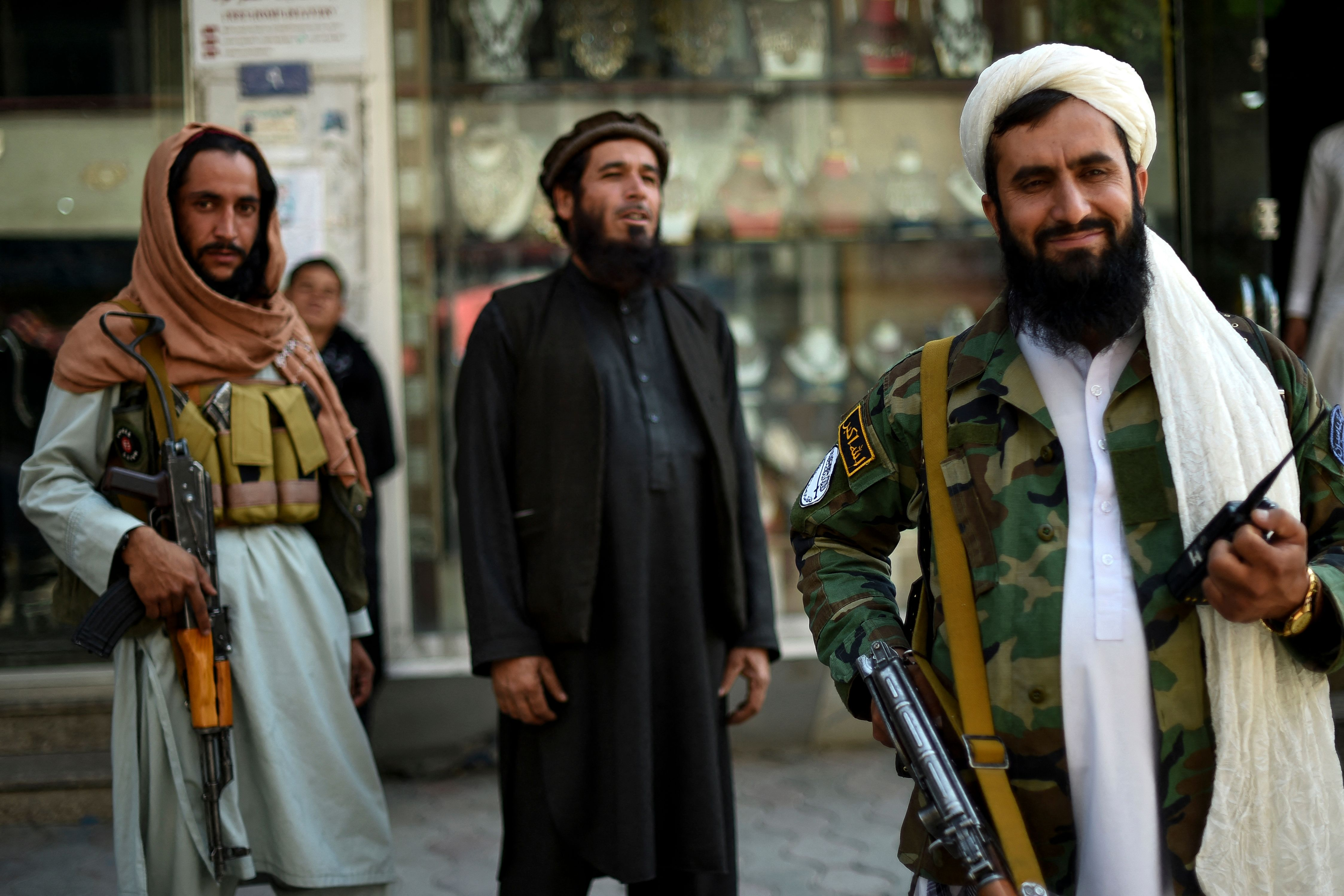 Taliban fighters stand guard on the backdrop of shops selling antiques and decorative merchandise at Chicken Street in Kabul on September 26, 2021.(Photo by WAKIL KOHSAR/AFP via Getty Images)