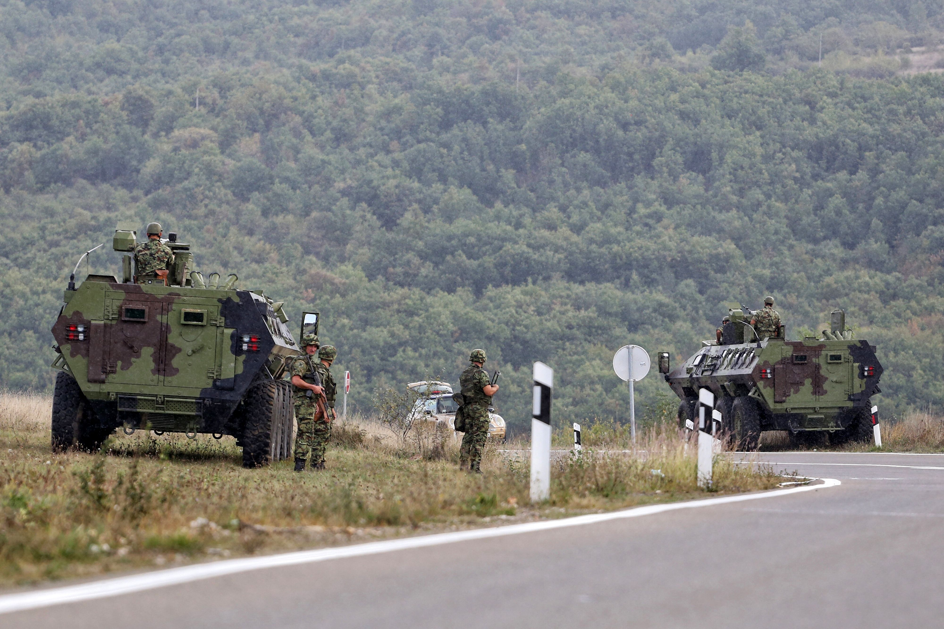 Serbian army soldiers stand guard by their armoured vehicles in the village of Rudnica near the southern Serbian town of Raska on September 27, 2021, where tensions are high at the border between Kosovo and Serbia as Belgrade deployed four armoured vehicles close to the frontier, an AFP correspondent saw.(Photo by IRFAN LICINA/AFP via Getty Images)