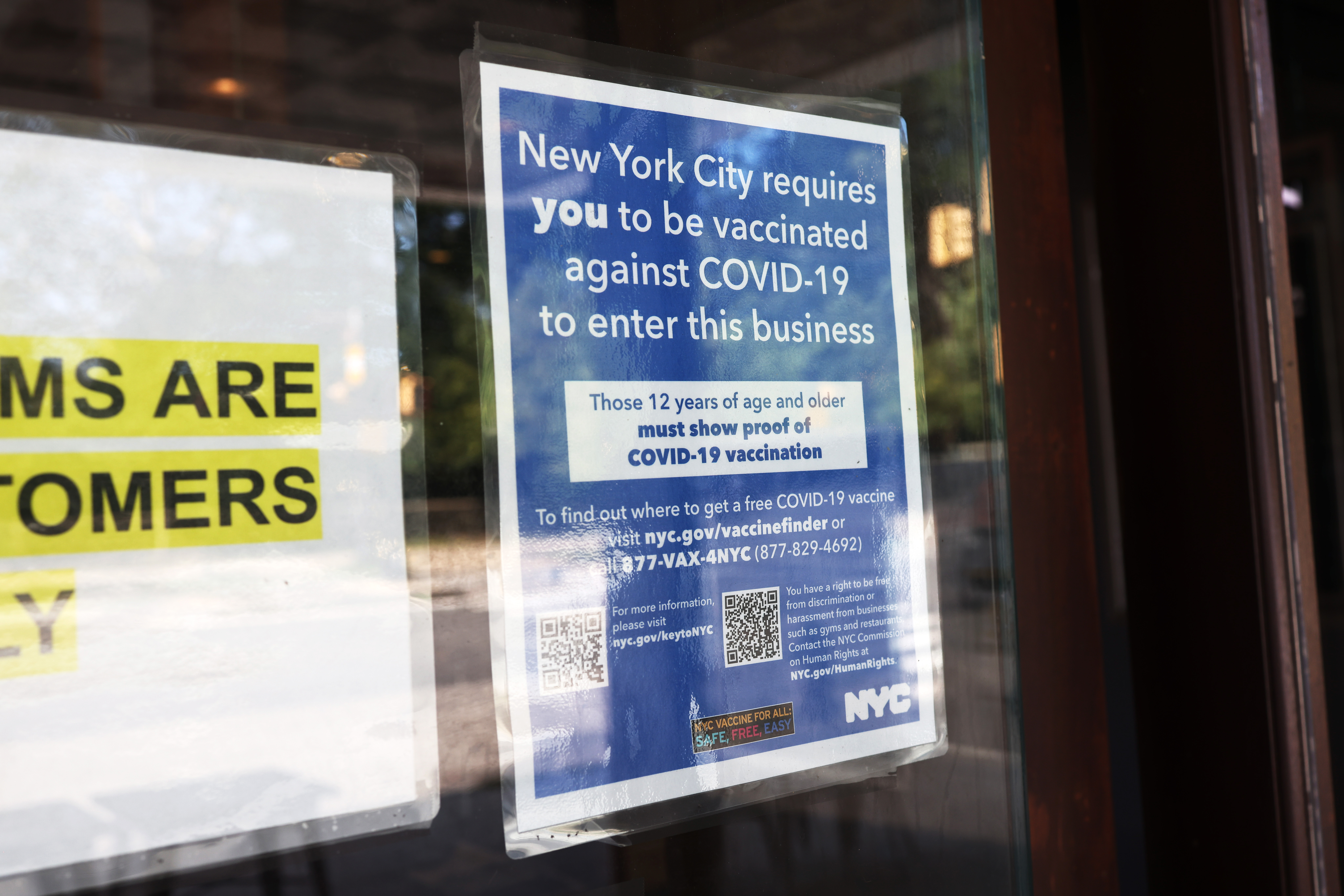 A coronavirus (COVID-19) vaccination sign is seen posted at the entrance of Nighthawk Cinema in the Park Slope neighborhood of Brooklyn in New York City. (Photo by Michael M. Santiago/Getty Images)
