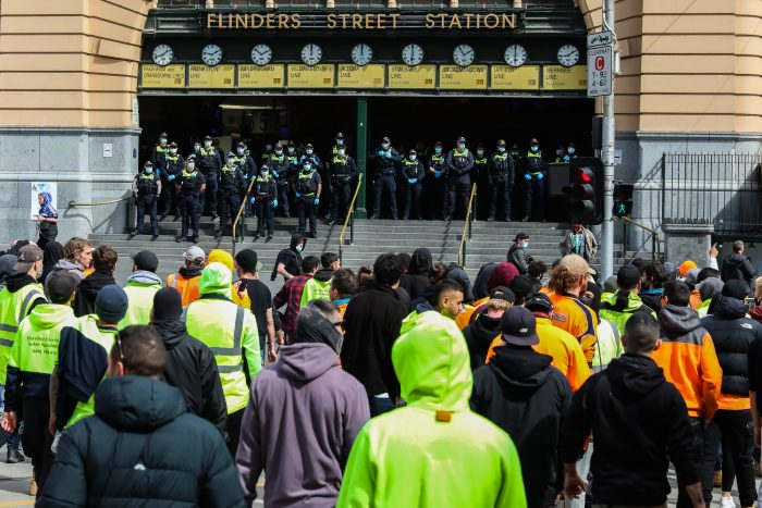 Protestors are seen walking past police outside Flinders Street station as thousands march through Melbourne after State Government announces construction shutdown on September 21, 2021 in Melbourne, Australia. (Photo by Asanka Ratnayake/Getty Images)