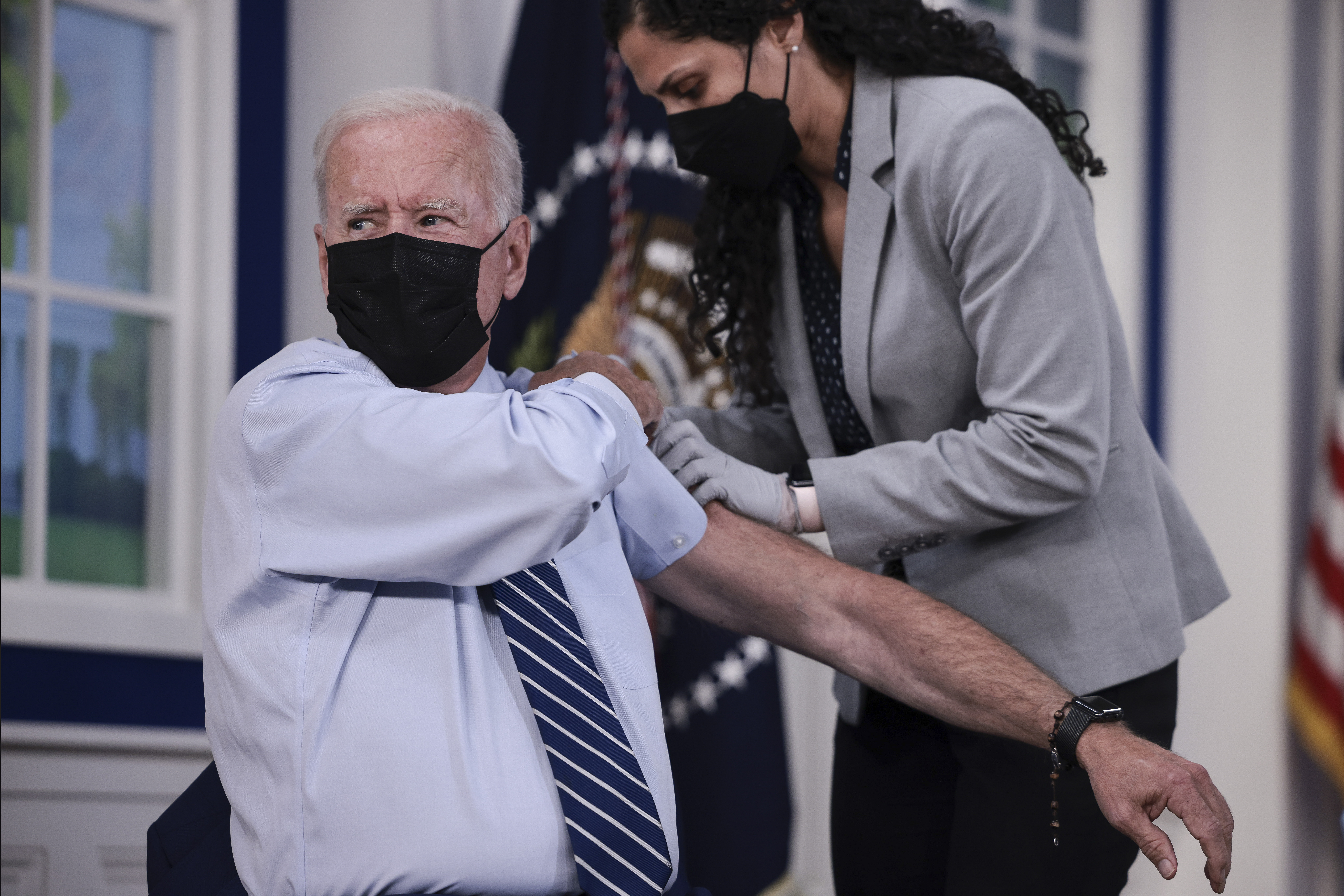 Joe Biden rolls up his sleeve before receiving a third dose of the Pfizer/BioNTech Covid-19 vaccine in the South Court Auditorium in the White House September 27, 2021 in Washington, DC. (Photo by Anna Moneymaker/Getty Images)
