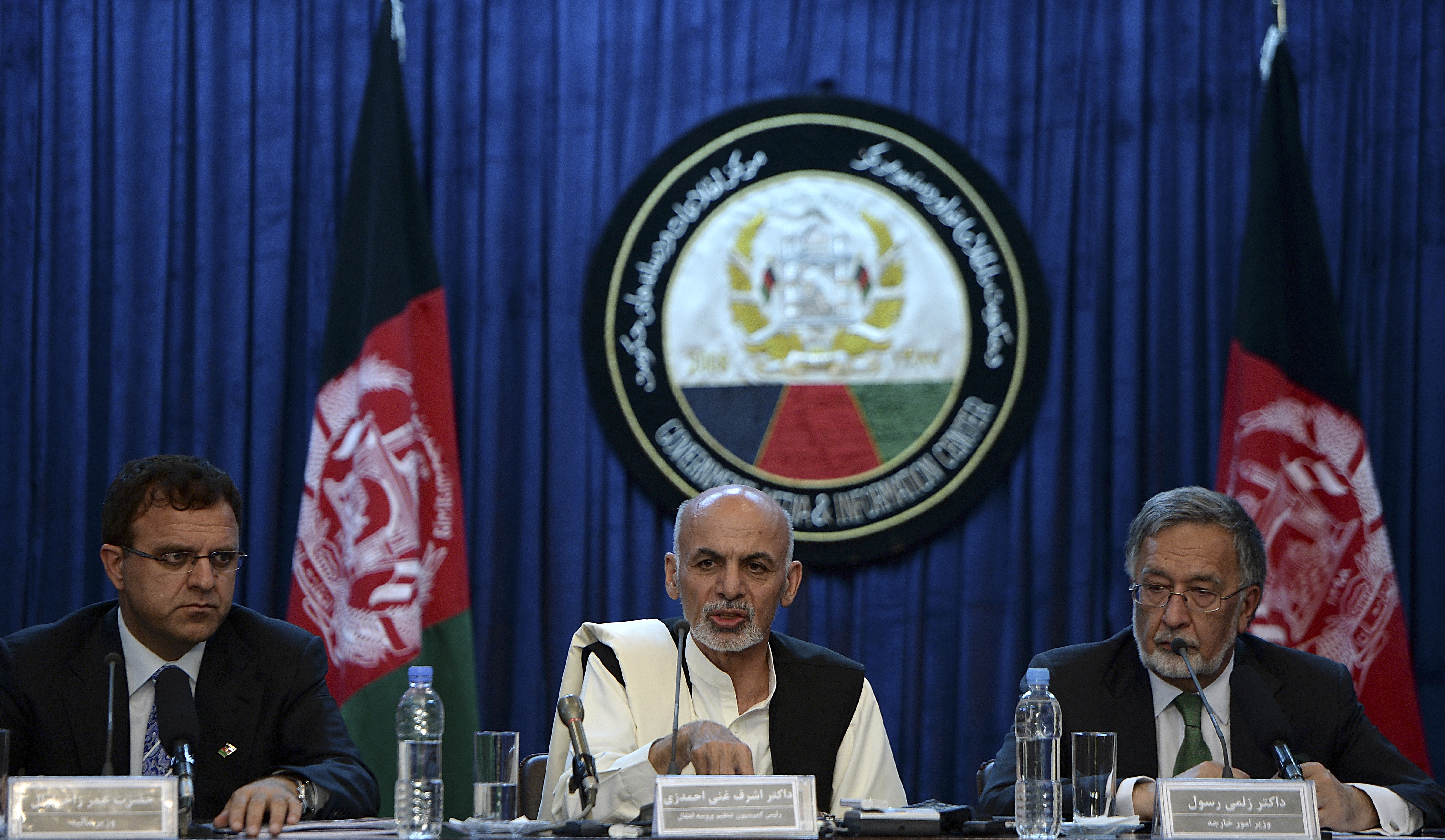 Former President Ashraf Ghani (center) speaks during a joint press conference while former Afghan Foreign Minister Zalmay Rassol (right) and former Afghan Finance Minister Omar Zakhilwal (left) look on in Kabul. (Photo by SHAH MARAI/AFP via Getty Images)