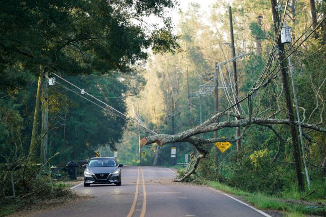 HAMMOND, LA - SEPTEMBER 1: A motorist passes under a storm damaged utility line on September 1, 2021 in Hammond, Louisiana. Tropical Storm Ida made landfall as a Category 4 hurricane Sunday in Louisiana and brought flooding, wind damage and power outages along the Gulf Coast. (Photo by Sean Rayford/Getty Images)