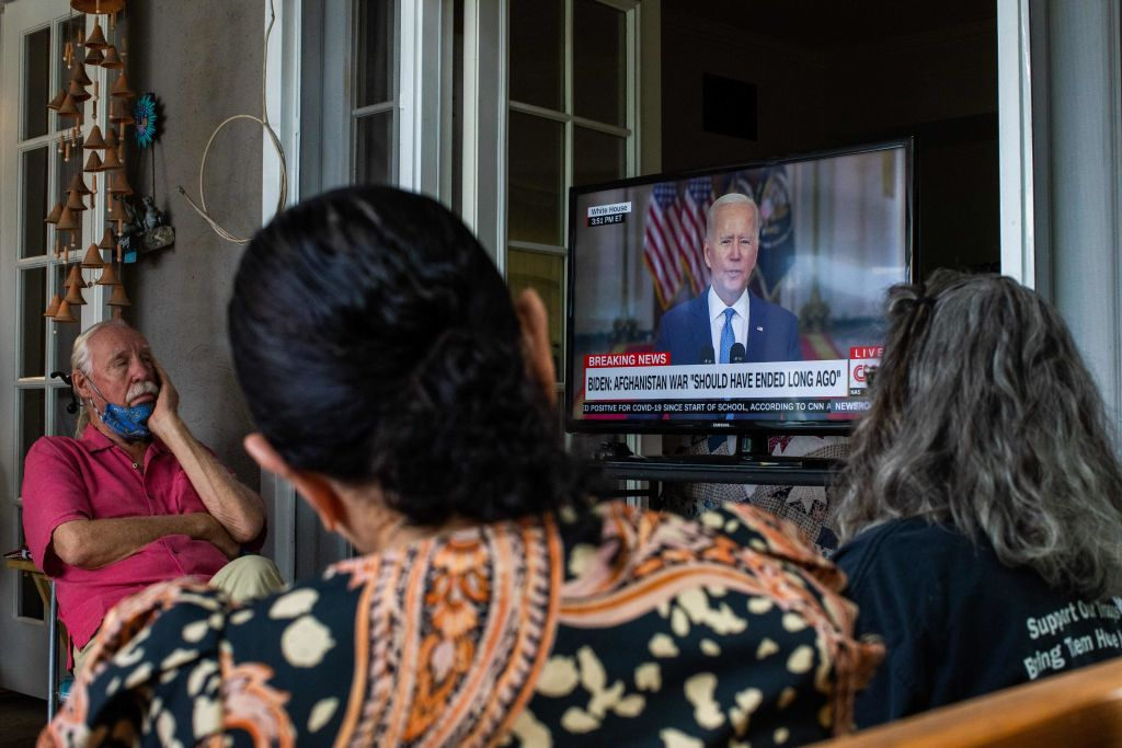 A group of military families and veterans,including a post 9-11 veteran who served in Afghanistan and the mother of a Marine who left Hamid Karzai International Airport last week gather in a home to watch President Joe Biden's speech announcing that all troops are out of Afghanistan, on August 31, 2021 in Long Beach California. - US President Joe Biden is addressing the nation on the US exit from Afghanistan after a failed 20 year war that he'd vowed to end but whose chaotic last days are now overshadowing his presidency. (Photo by Apu GOMES / AFP) (Photo by APU GOMES/AFP via Getty Images)