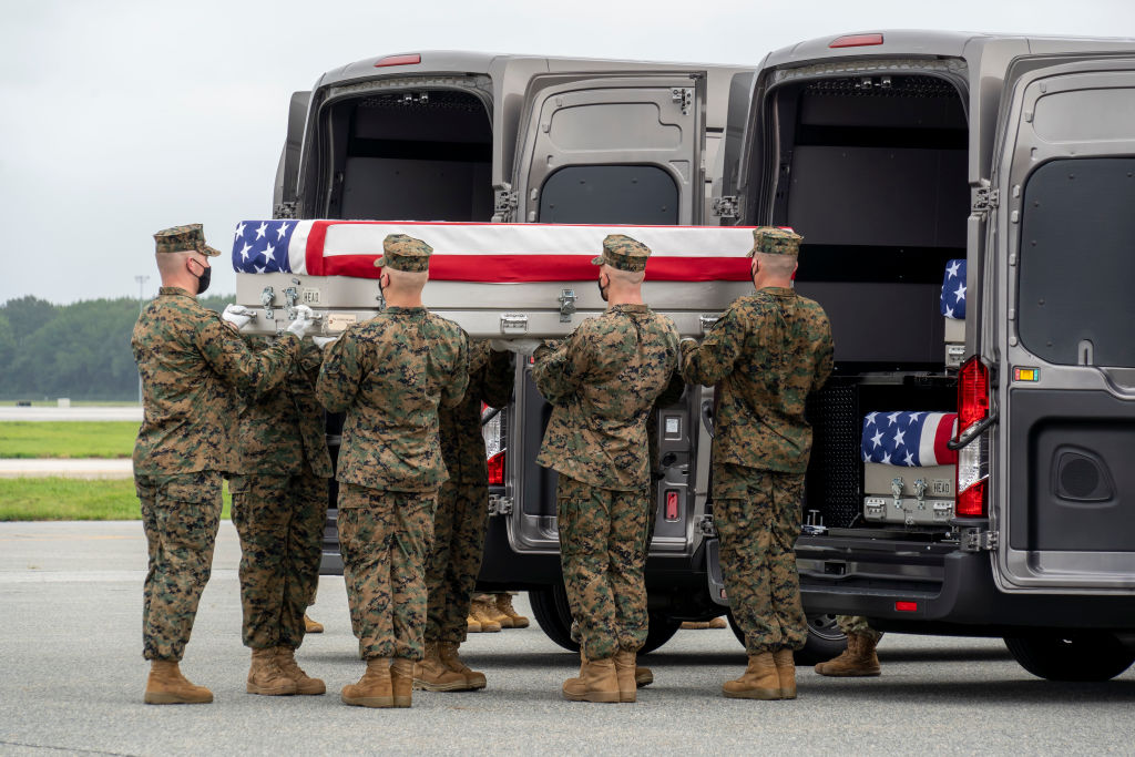 DOVER, DELAWARE - AUGUST 29: In this handout photo provided by the U.S. Air Force, a U.S. Marine Corps carry team transfers the remains of Marine Corps Lance Cpl. Kareem M. Nikoui of Norco, California, Aug. 29, 2021 at Dover Air Force Base, Delaware. Nikoui was assigned to 2nd Battalion, 1st Marine Regiment, 1st Marine Division, I Marine Expeditionary Force, Camp Pendleton, California. (Photo by Jason Minto/U.S. Air Force via Getty Images)